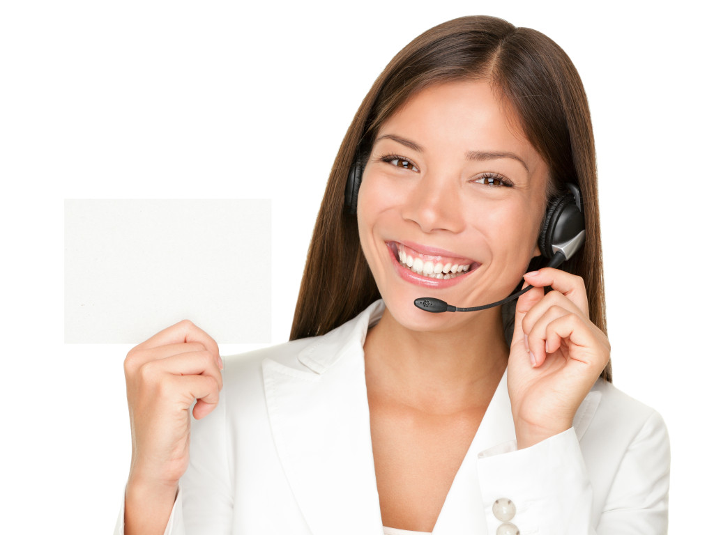 Headset. Customer service operator woman from call center smiling with headset showing blank empty sign card for copy space. Beautiful mixed race Asian Caucasian woman isolated on white background.